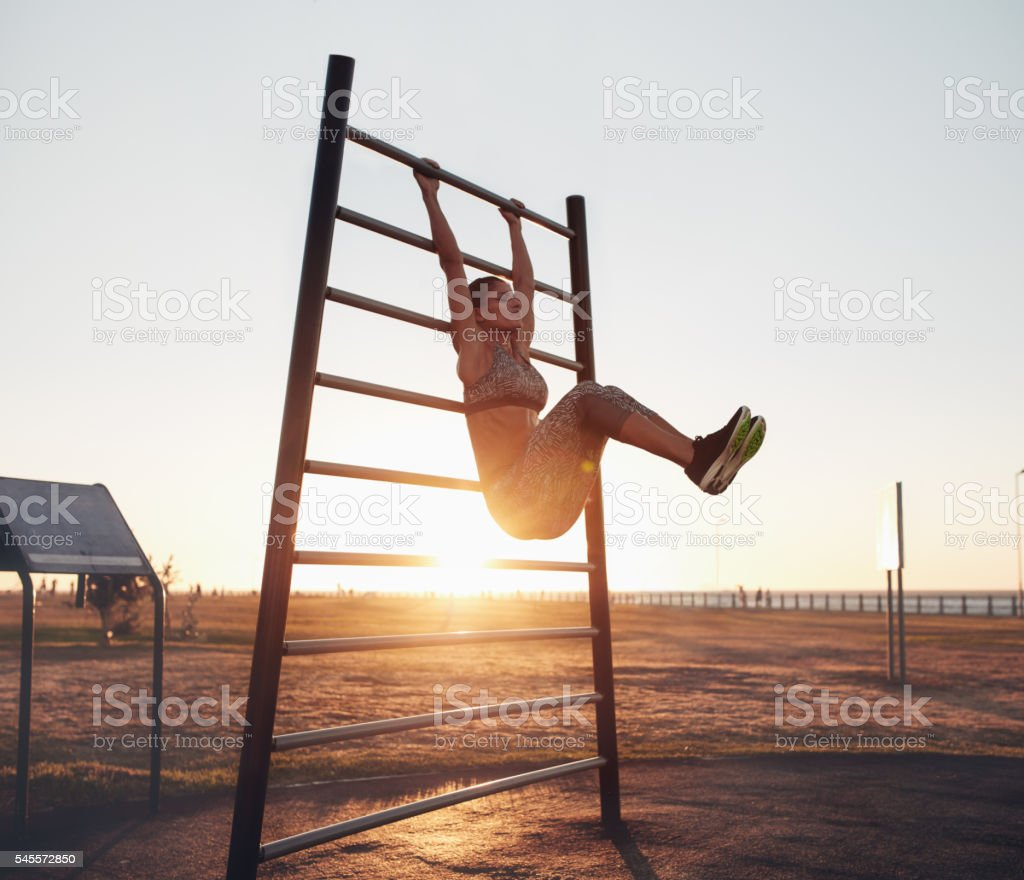 Young woman exercising on wall bars with her legs up stock photo