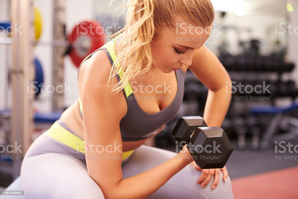 Young woman exercising with dumbbells at a gym, horizontal stock photo