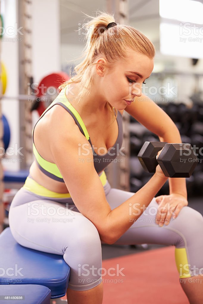 Young woman exercising with dumbbells at a gym, vertical stock photo