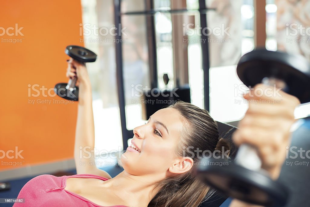 Young woman exercising with dumbbells in a gym royalty-free stock photo