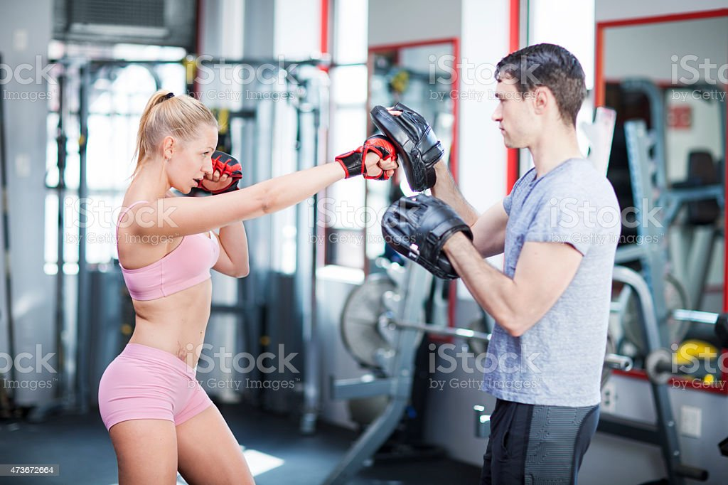 Young woman exercising with instructor stock photo
