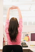 Young woman exercising with stretch in office cubicle