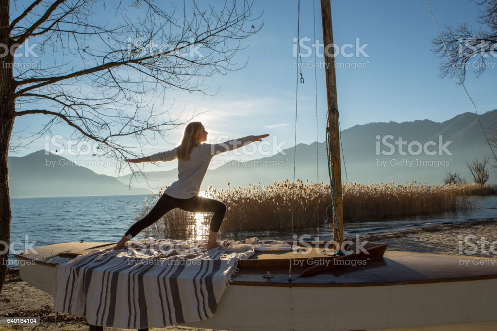 Young woman exercising yoga by the lake at sunset stock photo