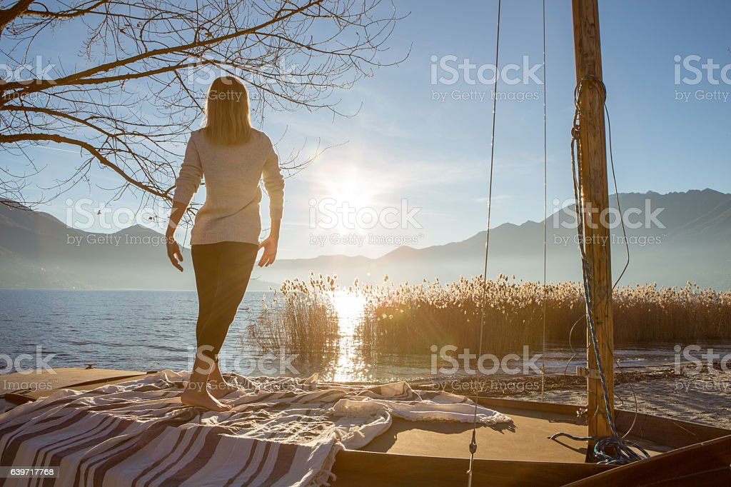 Young woman exercising yoga by the lake stock photo