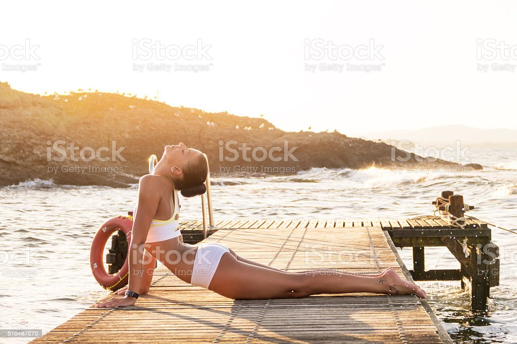 Young woman exercising yoga on the pier at sunset stock photo