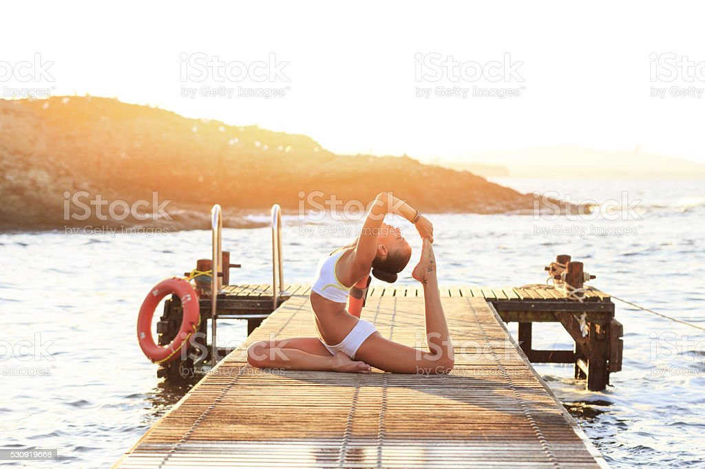 Young woman exercising yoga positions on pier at sunset stock photo
