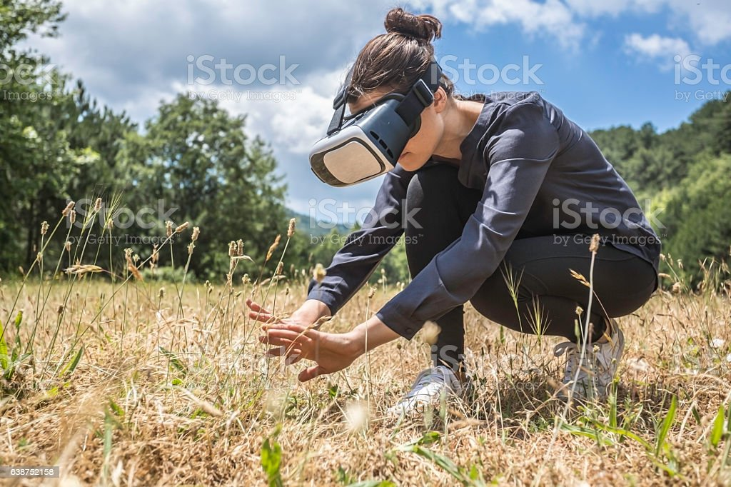 Young woman experiencing virtual reality of nature stock photo