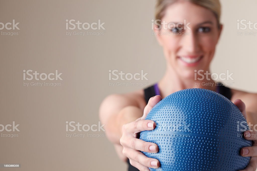 Young woman extending her arms while holding a medicine ball royalty-free stock photo