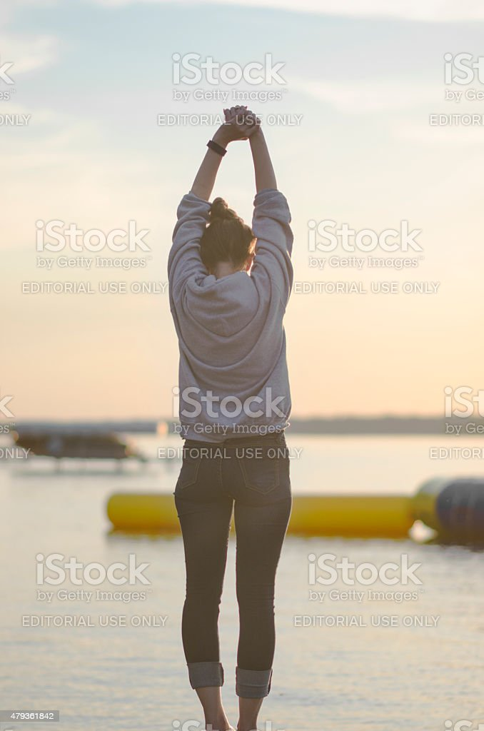Young Woman Facing Away From Camera Stretching Over Landscape stock photo