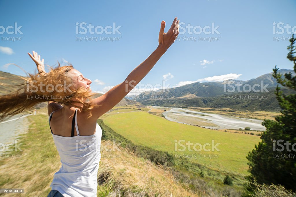 Young woman facing the strength of nature stock photo