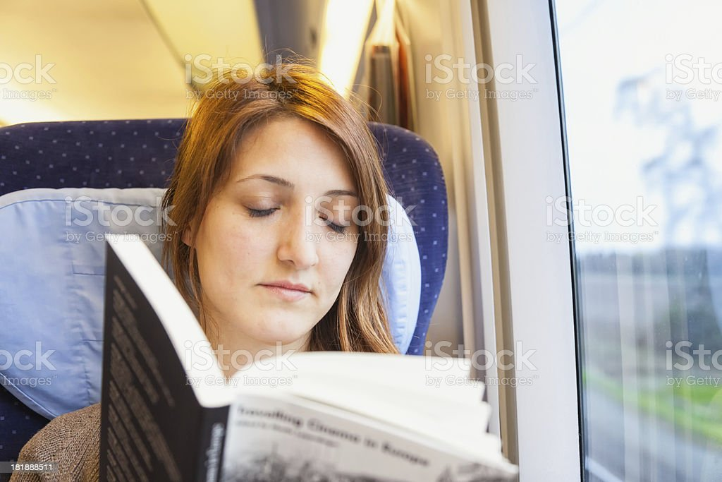 Young woman falling asleep while reading a book on train stock photo