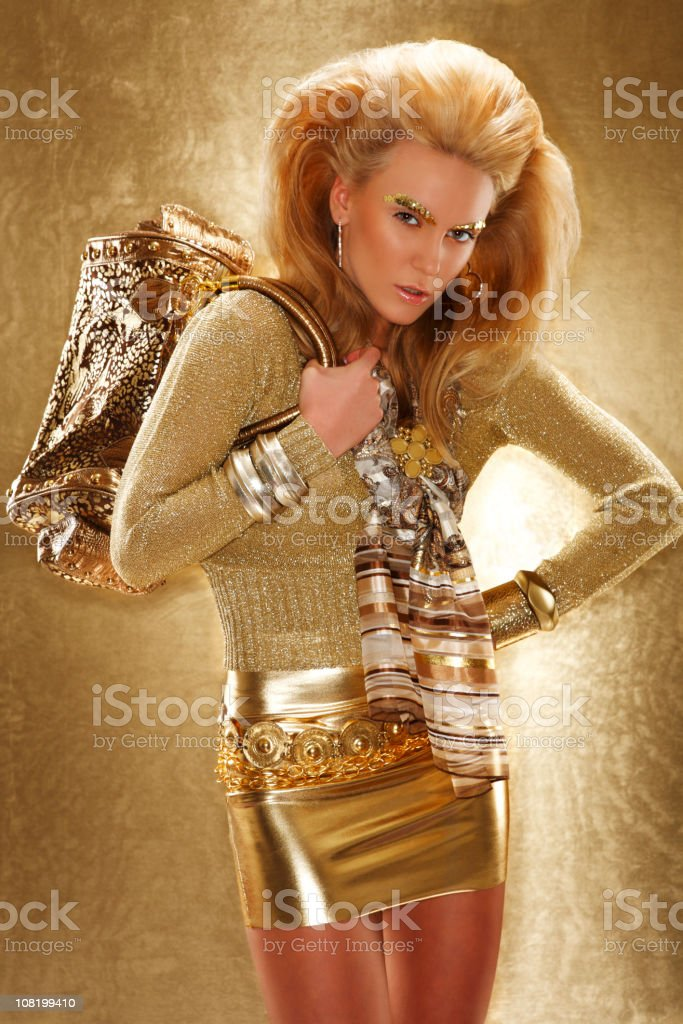 Young Woman Fashion Model Dressed in Gold Clothing and Make-Up royalty-free stock photo