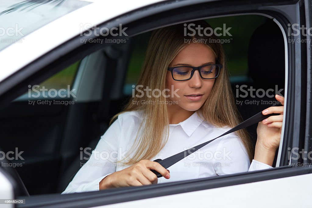 Young woman fasten seat belt stock photo