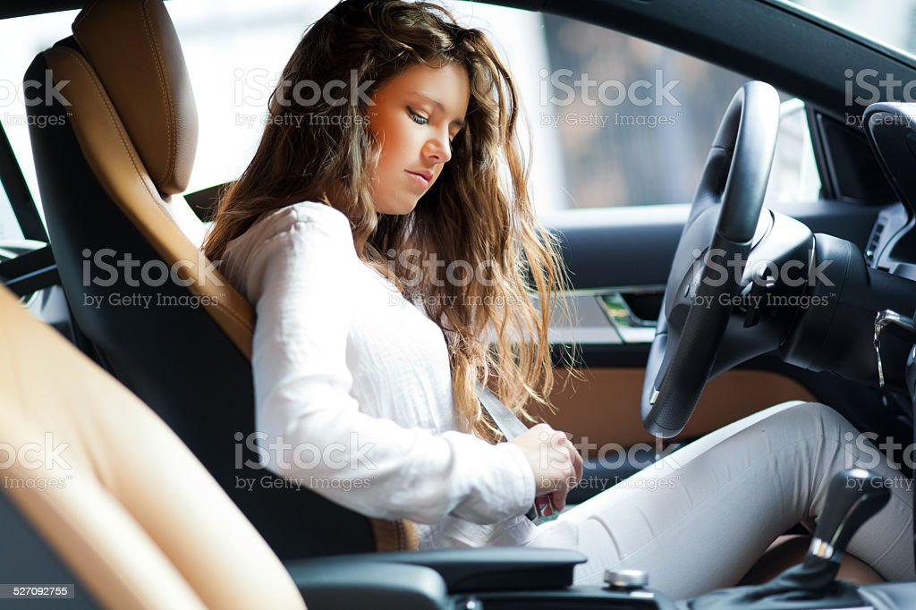 Young woman fastening the safety belt on her car stock photo