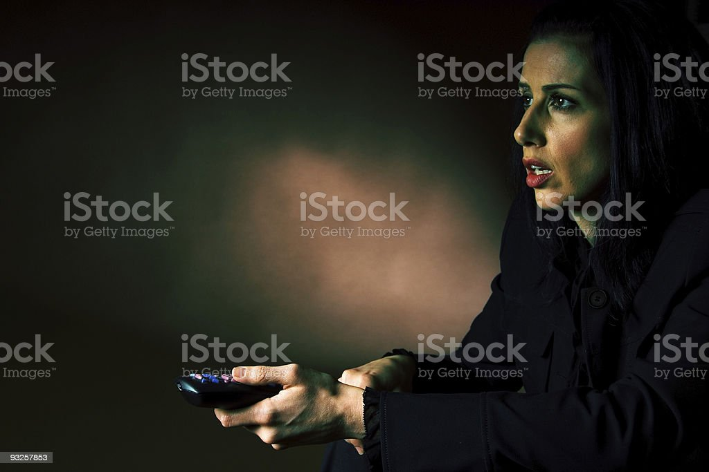 Young woman fearful of scary movie with remote stock photo