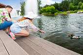 Young woman feeding ducks in a pond