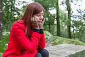 Young woman feeling depressed on a forest