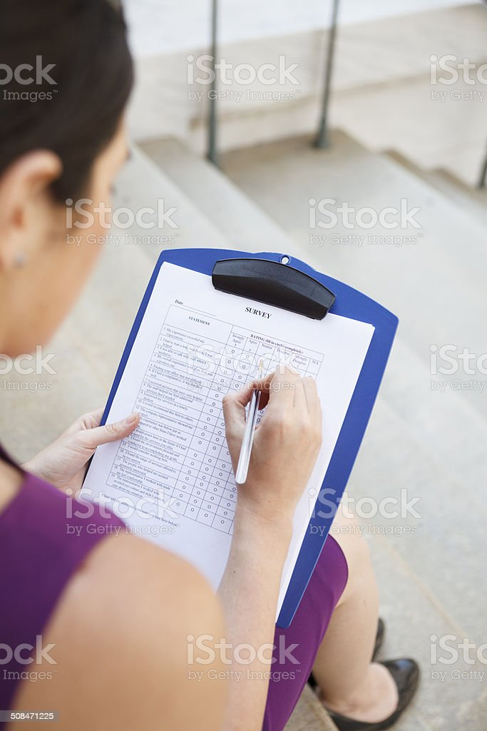 Young Woman Fills Out Survey royalty-free stock photo