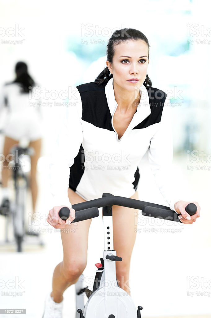 Young Woman Fitness Model Spinning on Staionary Bike in Gym royalty-free stock photo