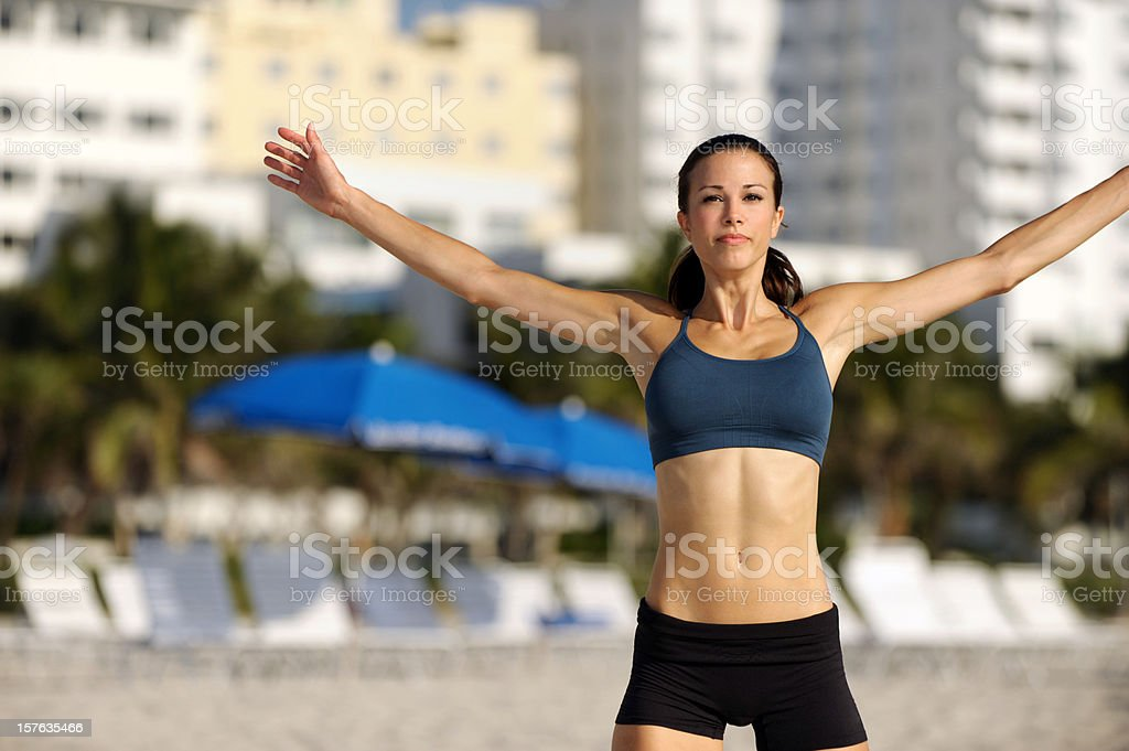Young Woman Fitness Trainer Jumping on Beach stock photo