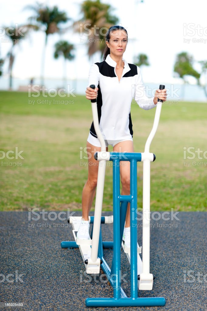 Young Woman Fitness Training on Stair Stepper in Park stock photo
