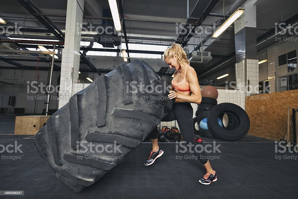 Young woman flipping tire at gym stock photo