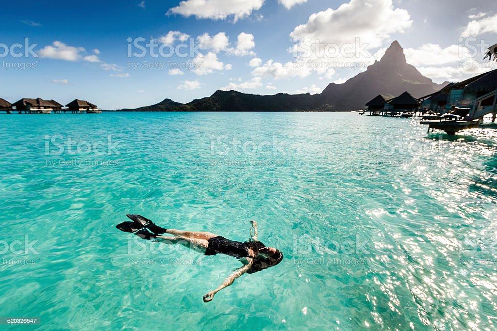Young Woman Floating in Wonderful Sea of Bora Bora stock photo