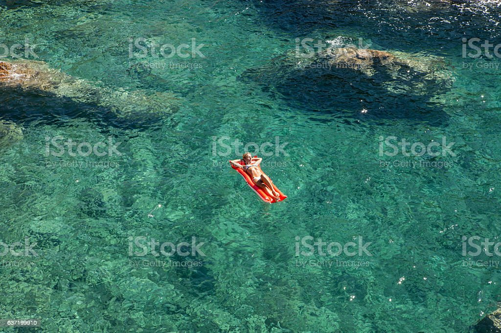 Young woman floating on pool mattress in the ocean stock photo