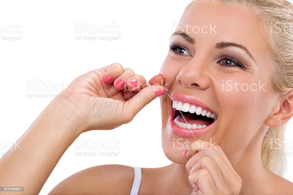 Young woman flossing her teeth stock photo