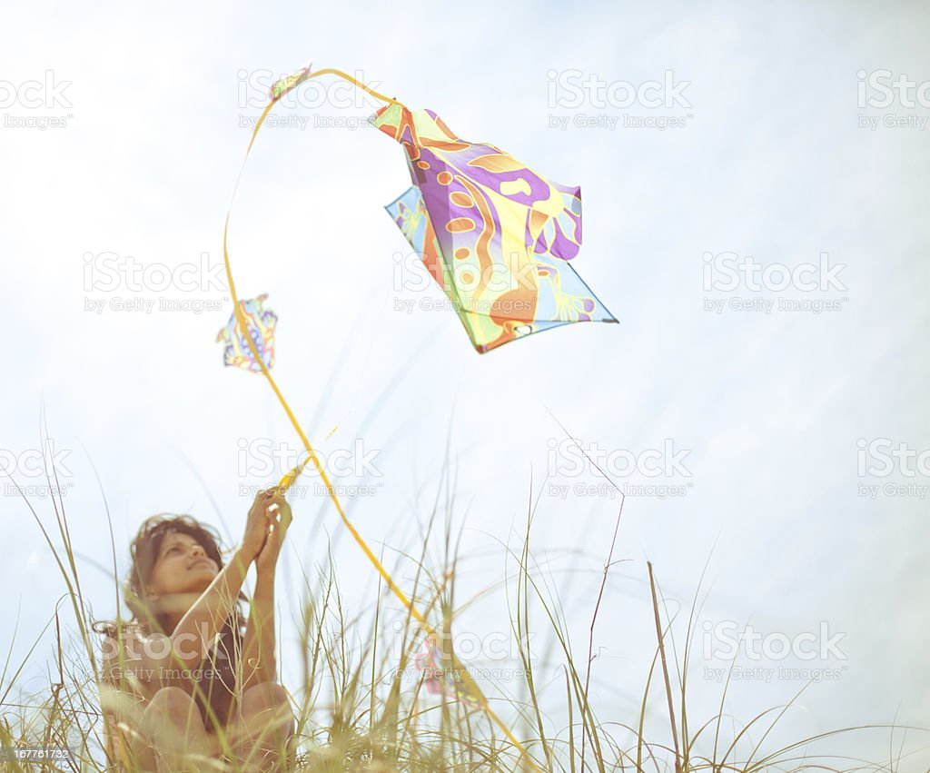 Young woman flying kite on summery day at the beach stock photo