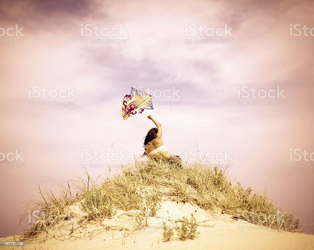Young woman flying kite on summery day at the beach royalty-free stock photo