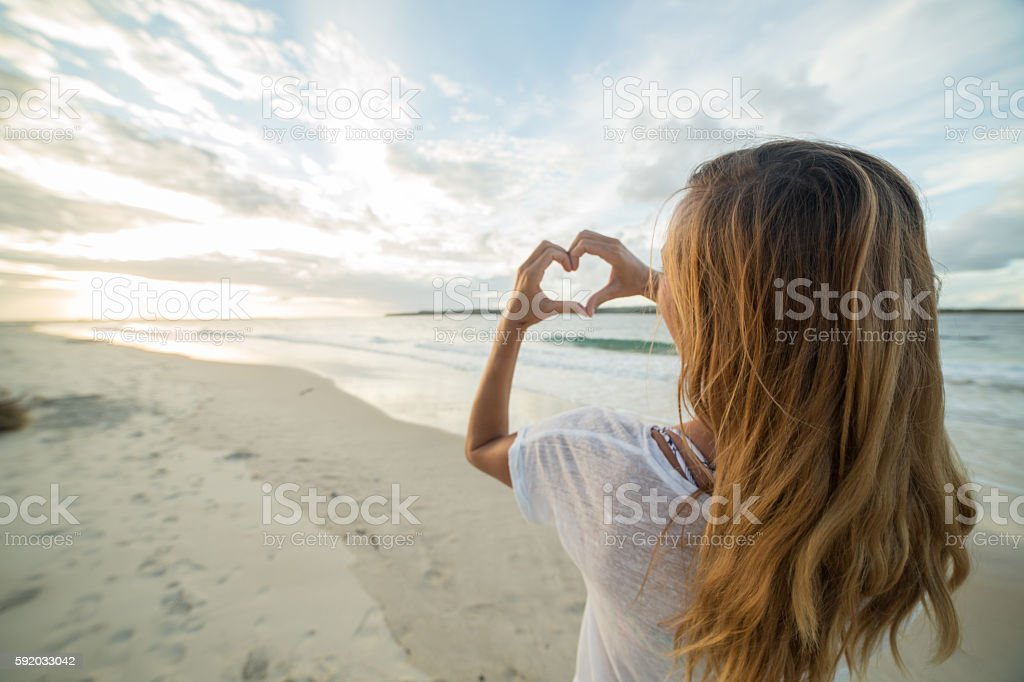 Young woman frames sunset on beach into heart shape stock photo