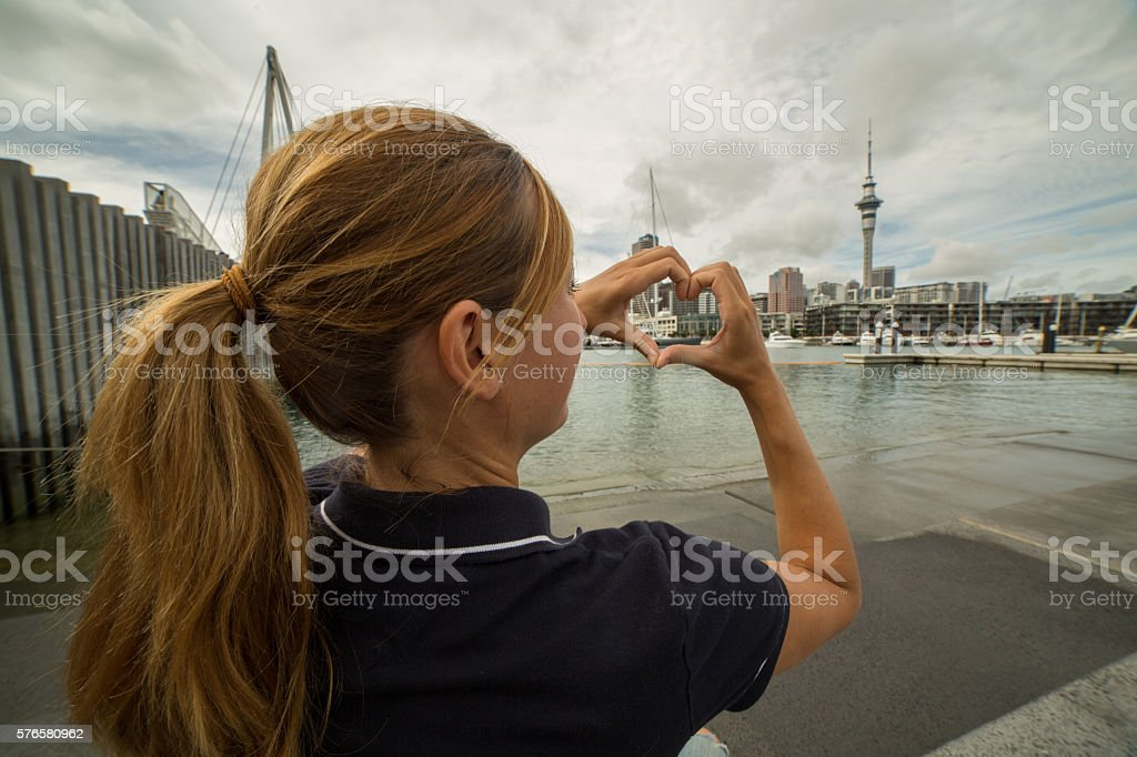 Young Woman Framing Auckland Skyline Into Heart Shape Finger Frame ...