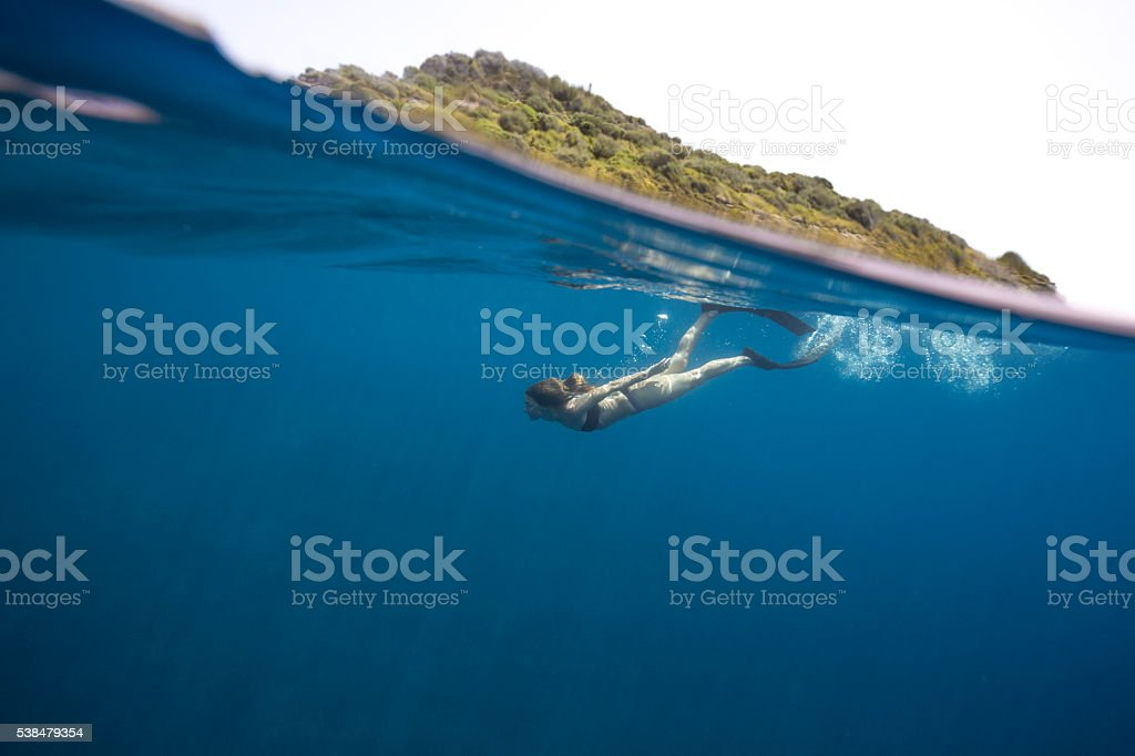Young woman free diving underwater split shot stock photo