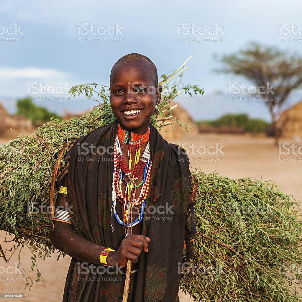 Young woman from Erbore tribe carrying grass, Ethiopia, Africa royalty-free stock photo