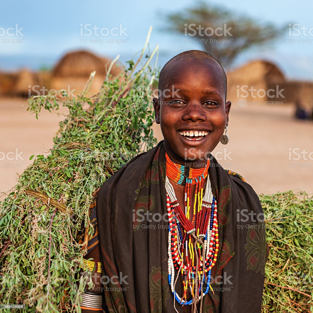 Young woman from Erbore tribe carrying grass, Ethiopia, Africa stock photo