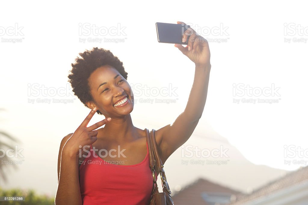 Young woman gesturing peace sign and taking a selfie stock photo