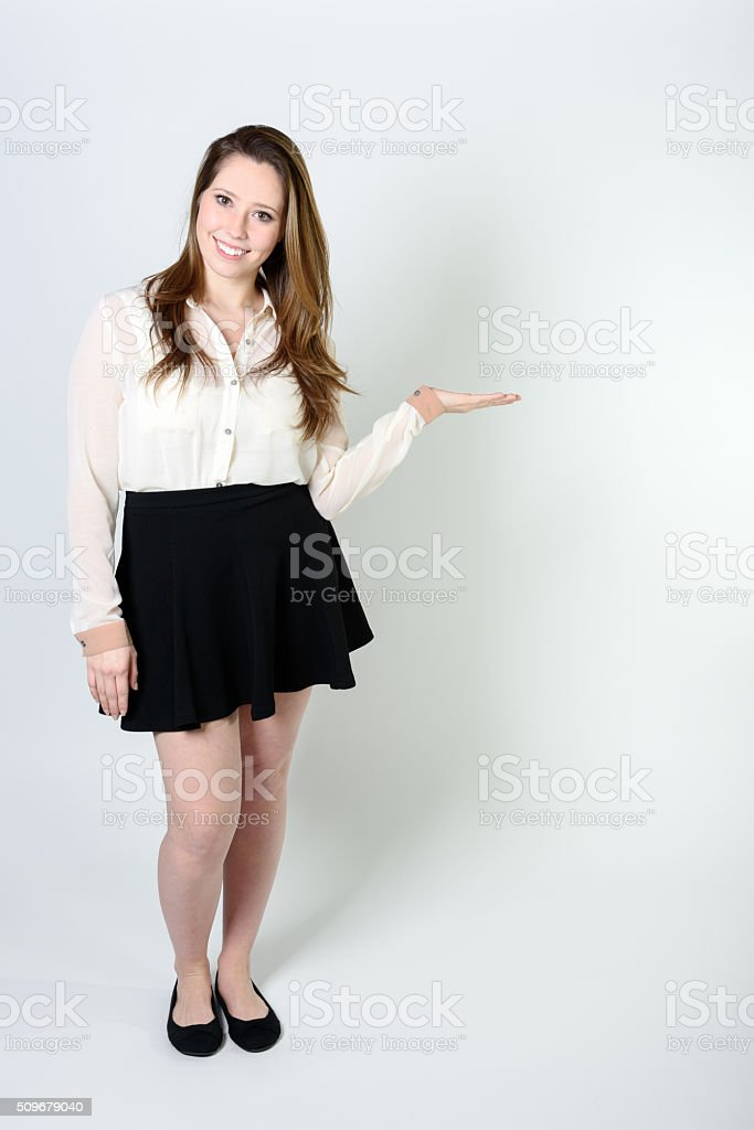 Young woman gesturing toward copyspace stock photo