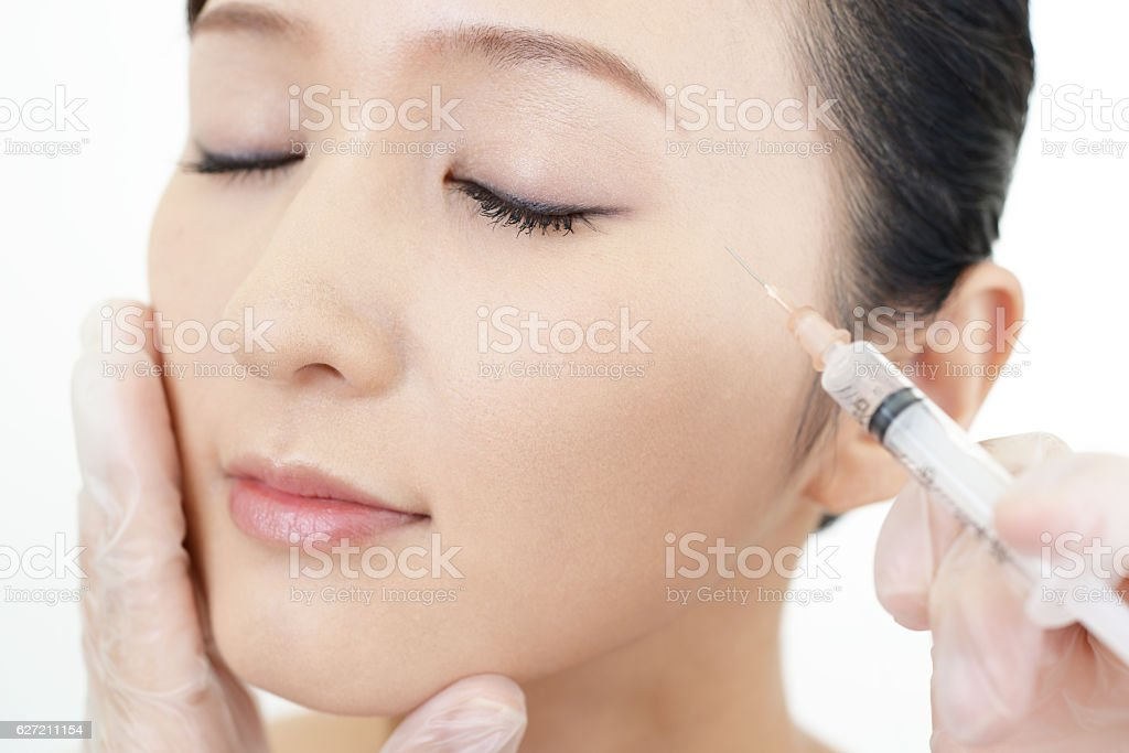 Young woman gets beauty injection in her face stock photo