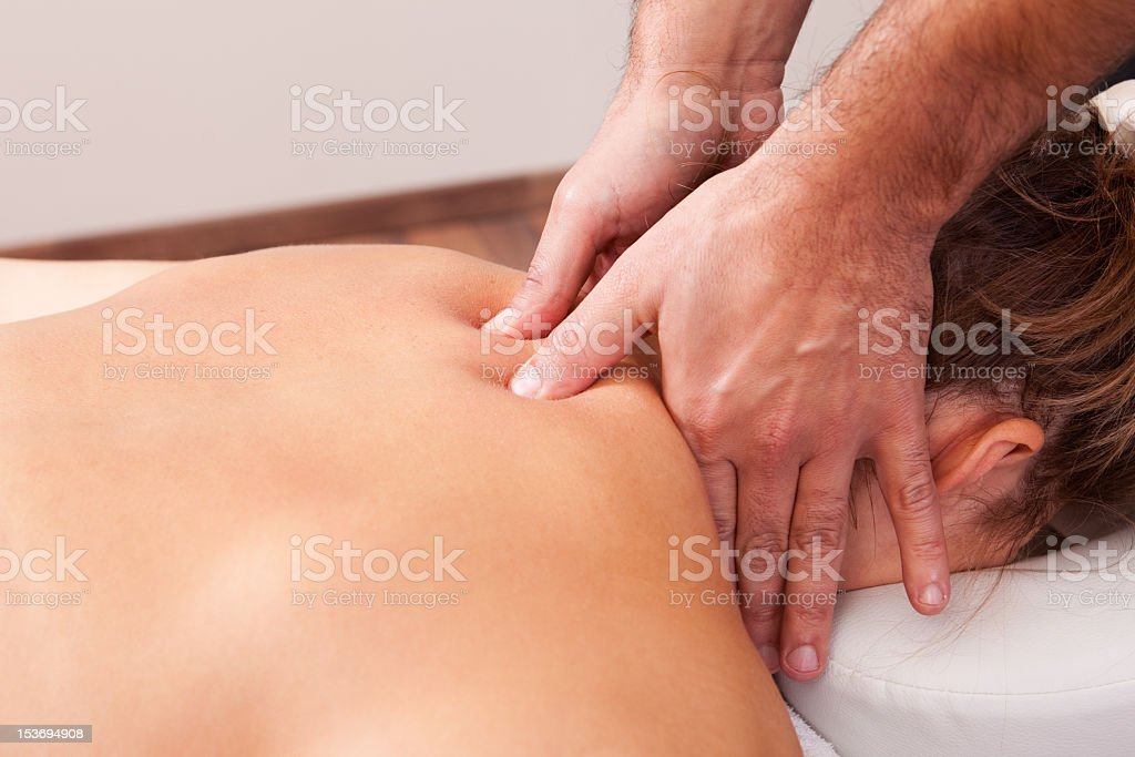Young woman getting a back massage by a professional royalty-free stock photo