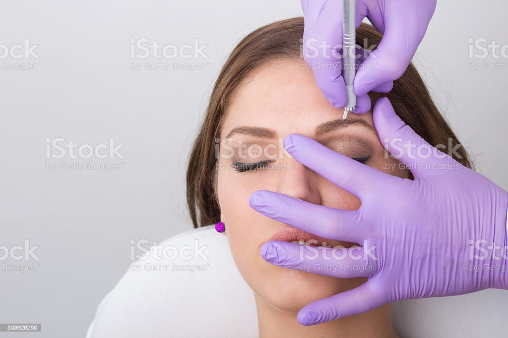 Young woman getting a permanent eyebrow make up treatment stock photo