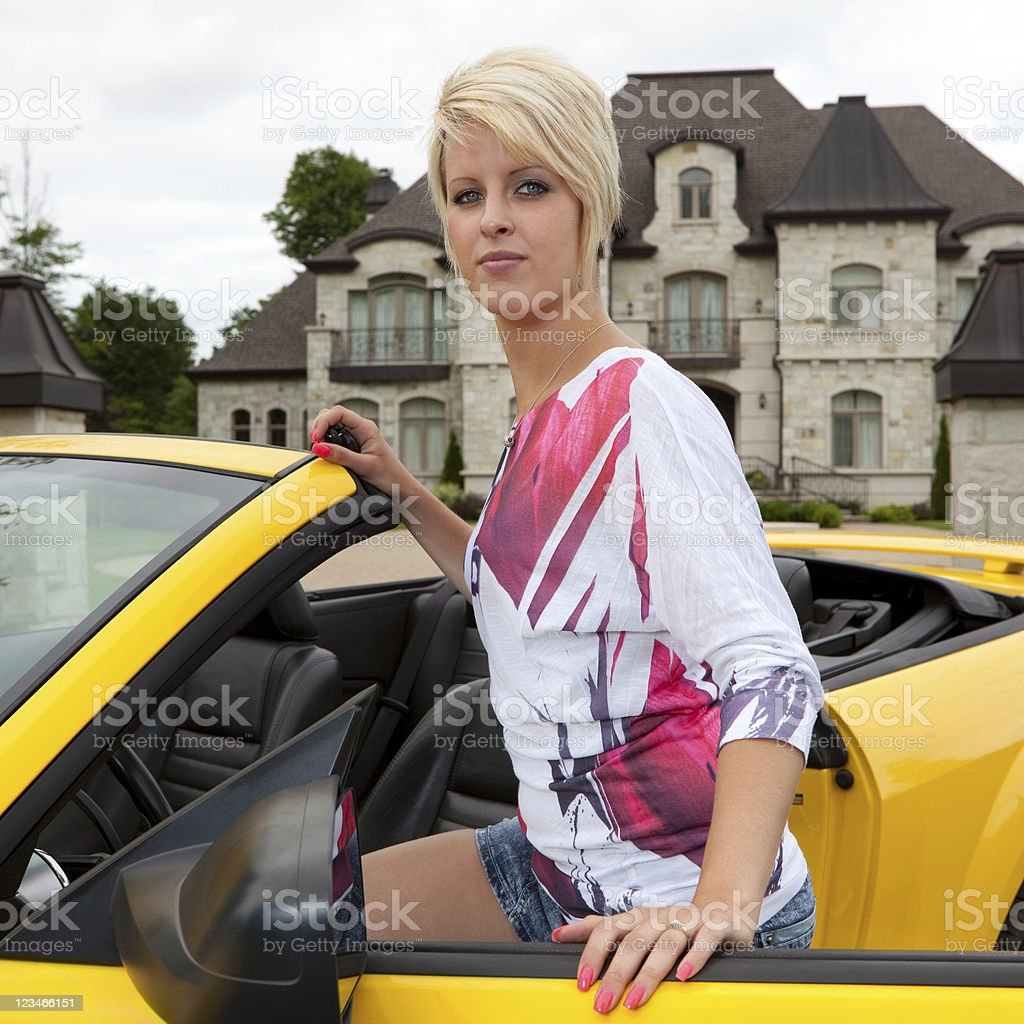 Young woman getting into a convertible car stock photo