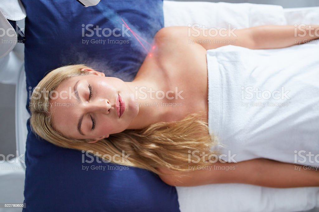 Young woman getting local cryotherapy treatment stock photo