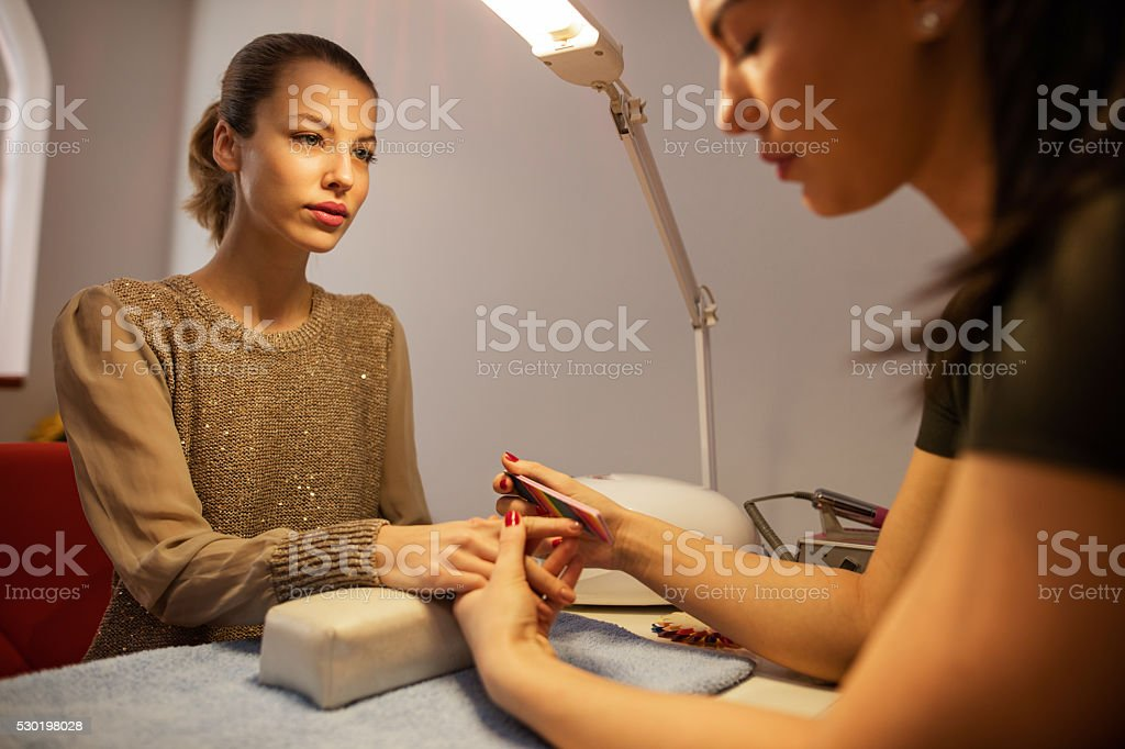 Young woman getting manicure at beauty salon. stock photo