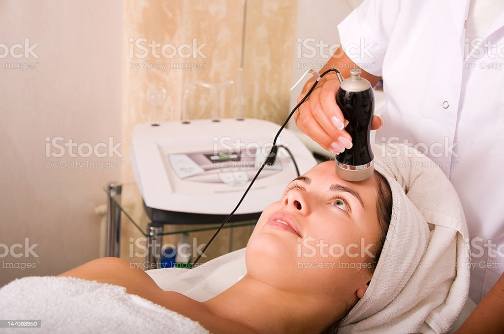 Young woman getting skin cleaning at beauty salon (shallow dof) royalty-free stock photo
