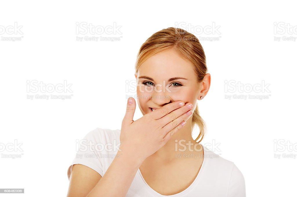 Young woman giggles covering her mouth with hand stock photo
