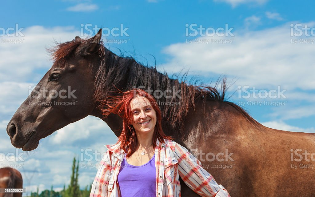 Young woman girl taking care of horse. stock photo