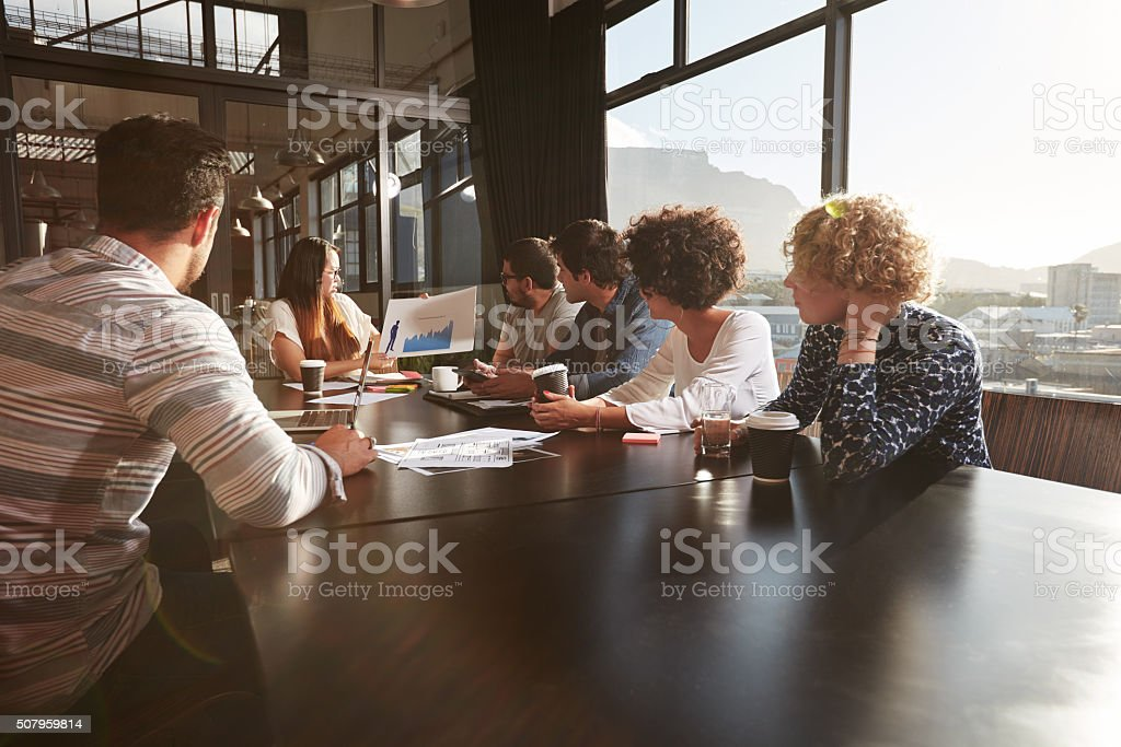 Young woman giving a presentation to colleagues stock photo
