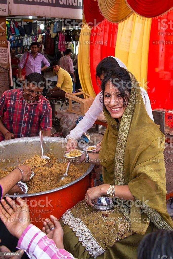 Young woman giving away rice at Guru Nanak Gurpurab celebration, stock photo