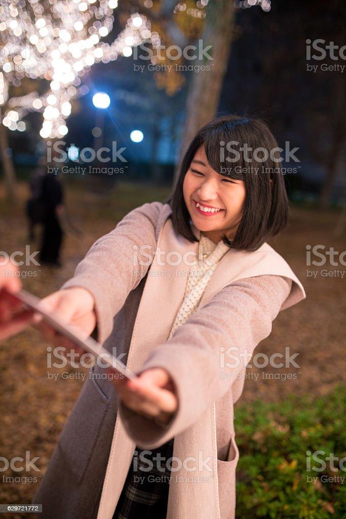 Young woman giving card at Christmas night stock photo